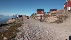 Village and people in mountains on shore of Arctic Ocean from Greenland. Stock Footage
