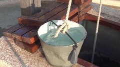 A bucket full of water put on the edge of a water well. Stock Footage