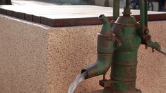 Hand water pump pouring water next to a well. Stock Footage