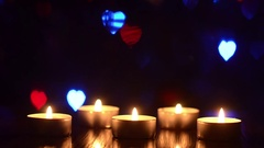 Burning candles on a table in a dark room, blinking colorful bokeh hearts blue Stock Footage
