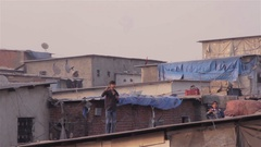 A young boy flying a kite in slum area, Stock Footage