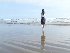 Japanese girl in school uniform smiling at the camera on the beach, Chiba Stock Footage