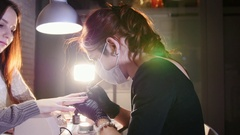 Professional nails care in process, cosmetician with mask in black gloves making Stock Footage