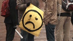 Person holding a classic sad face sign in Pioneer Square in downtown Portland. Stock Footage