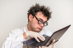 Crazy scientist in glasses with laptop working in his laboratory Kuvituskuvat