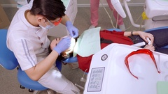 Doctor work tool for cleaning plaque from a girl customer. Ultra High Definition Stock Footage