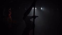 Flexible pole dancer posing upside down on pylon, slow motion. Stock Footage