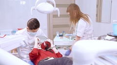 Doctor prepared for the procedure, adjusts the lamp and blows air to the oral Stock Footage