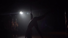 Young woman exercising pole dance fitness, slow motion. Silhouette. Stock Footage