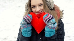 Happy girl holding handmade heart and smiling to the camera, steadycam shot Stock Footage