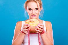 Woman holds sweet bun recommending non sugar diet Stock Photos