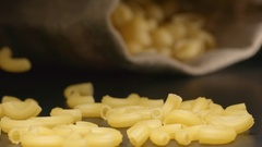 SLOW MOTION: Pasta fall near a lying cloth bag Stock Footage