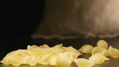 SLOW MOTION: Pasta (conchiglie) fall near a cloth bag Stock Footage