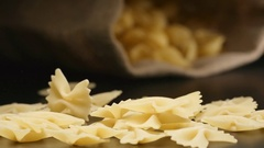 SLOW MOTION: Figural pasta (farfalle) fall near a lying cloth bag Stock Footage