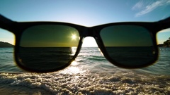 Look at the beautiful sea and sunset beach through sunglasses РОV. Concept of Stock Footage