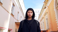 A young man in a black stylish dress walking around the old town Stock Footage