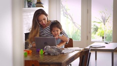 Mother And Daughter Watch Movie On Laptop At Home Together Stock Footage