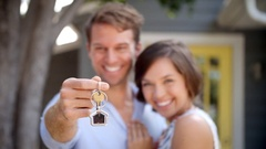 Portrait Of Happy Couple Standing Outside New Home With Keys Stock Footage
