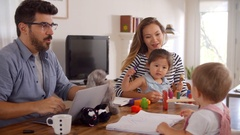 Father Uses Laptop Whilst Mother Plays With Children At Home Stock Footage