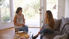 Two Female Friends Socializing Together At Home Stock Footage