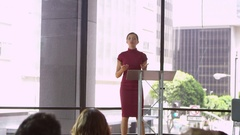 Young woman at a lectern presenting a business seminar Stock Footage