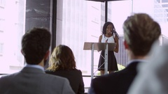 Audience at seminar applauding young black woman at lectern Stock Footage