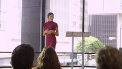 Young woman on stage presenting a business seminar Stock Footage