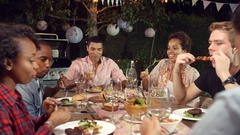 Young adult friends eat and drink at an outdoor dinner party Stock Footage