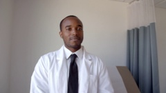 Portrait Of Male Doctor Wearing White Coat In Exam Room Stock Footage