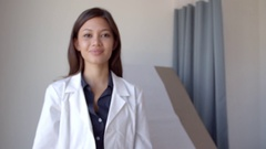 Portrait Of Female Doctor Wearing White Coat In Exam Room Stock Footage