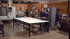 Engineers Working On Machines In Busy Metal Workshop Stock Footage