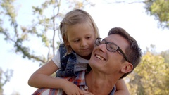 Dad and young daughter pulling faces in a park, front view Stock Footage