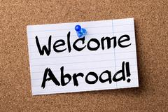 Welcome Abroad! - teared note paper pinned on bulletin board Stock Photos