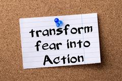 Transform fear into Action - teared note paper pinned on bulletin board Stock Photos