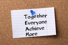 Together Everyone Achieve More TEAM - teared note paper pinned on bulletin .. Stock Photos