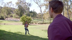 Seven year old boy throwing football with his dad in park Stock Footage