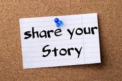 Share your story - teared note paper pinned on bulletin board Stock Photos