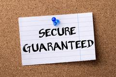 SECURE GUARANTEED - teared note paper pinned on bulletin board Stock Photos