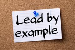 Lead by example - teared note paper pinned on bulletin board Stock Photos