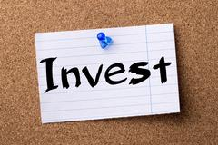 Invest - teared note paper pinned on bulletin board Stock Photos