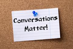 Conversations Matter! - teared note paper pinned on bulletin board Stock Photos