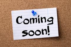 Coming soon! - teared note paper  pinned on bulletin board Stock Photos