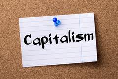 Capitalism - teared note paper pinned on bulletin board Stock Photos