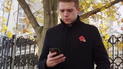 Man Wearing Remembrance Day Poppy Using Mobile Phone Stock Footage