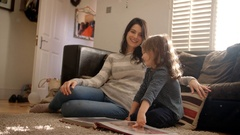 Mother And Daughter At Home Looking Through Photo Album Stock Footage