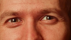 The eyes of a young white male close-up shot. they winks and laughs, visible Stock Footage