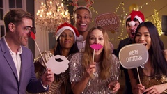 Group Of Friends Dressing Up For Christmas Party Together Stock Footage