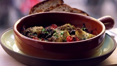 Cod and chorizo bake with sourdough bread by window, pan Stock Footage