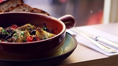 Cod and chorizo bake in earthenware dish by window, pan Stock Footage