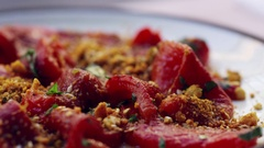 Plate of marinated, flamed red peppers, extreme close up pan Stock Footage